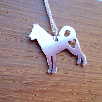 Dog with heart cutout pendant